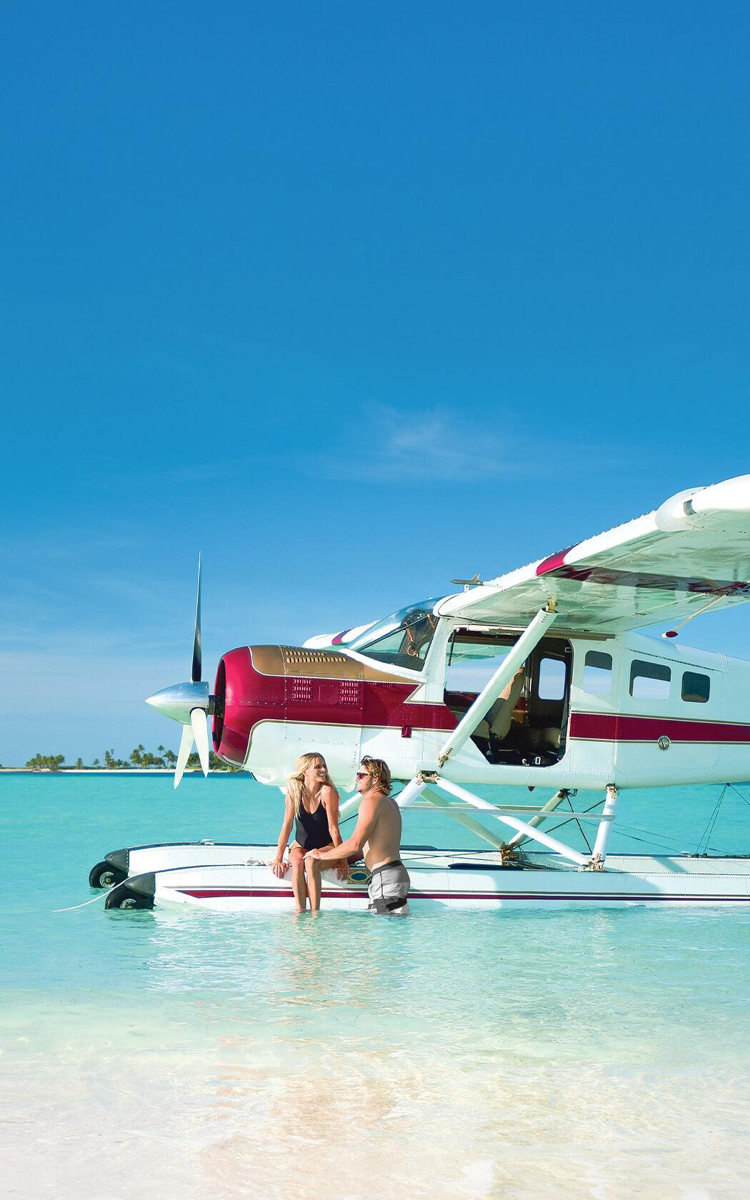 couple sitting on a seaplane's float