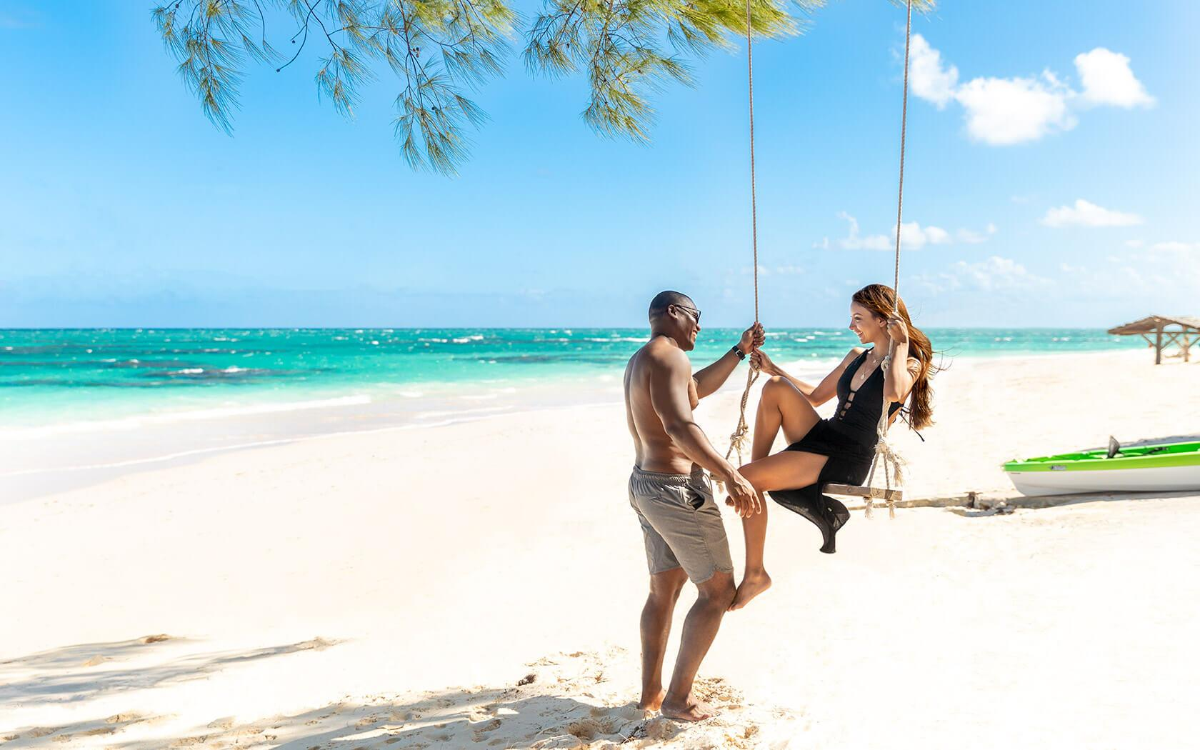 man and woman flirting on beach swing
