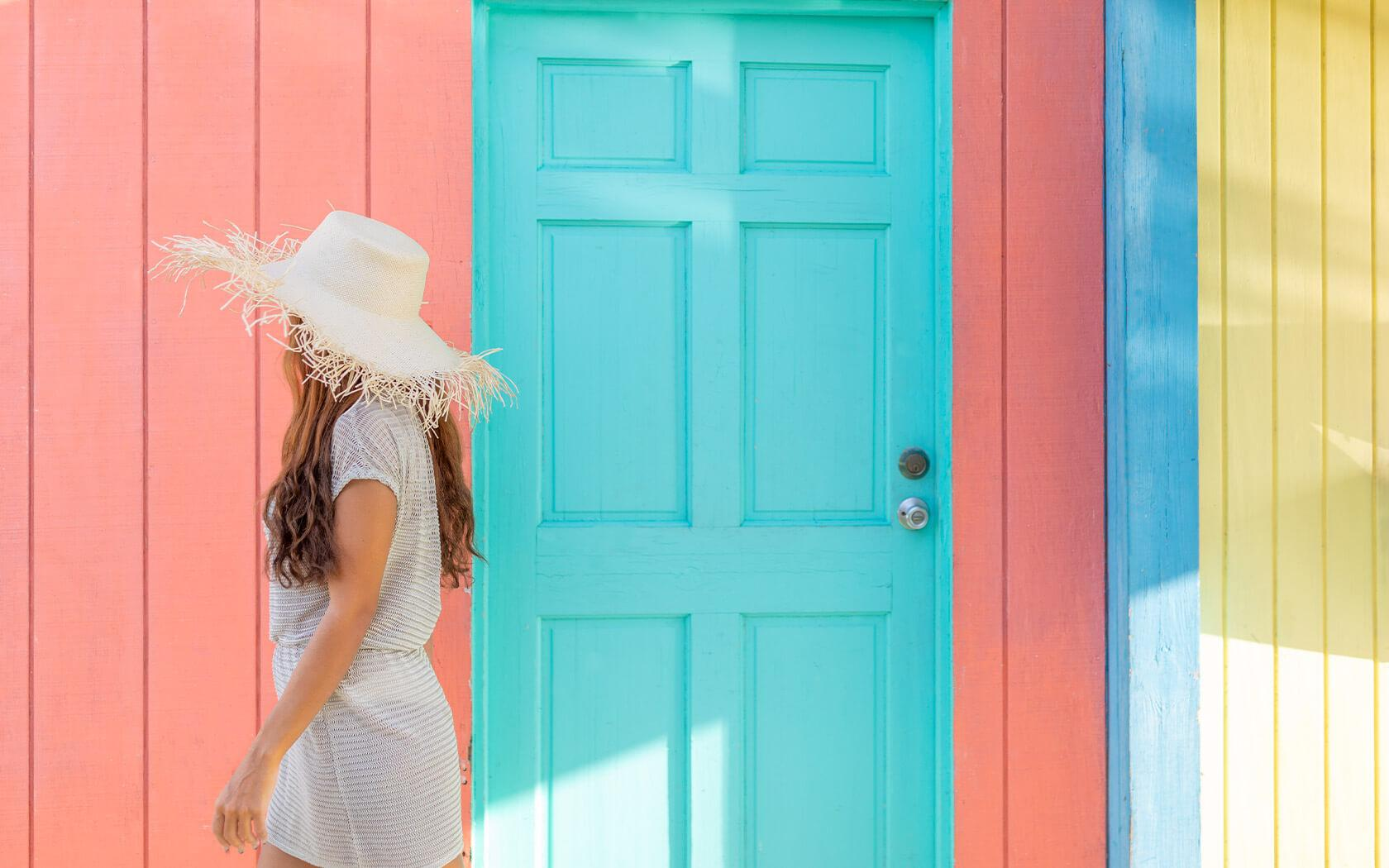 woman in a straw hat walking past brightly colored walls and door