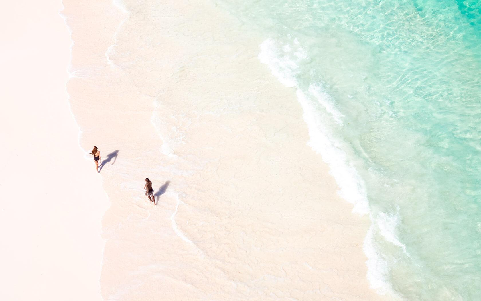 aerial view of two people running on beach