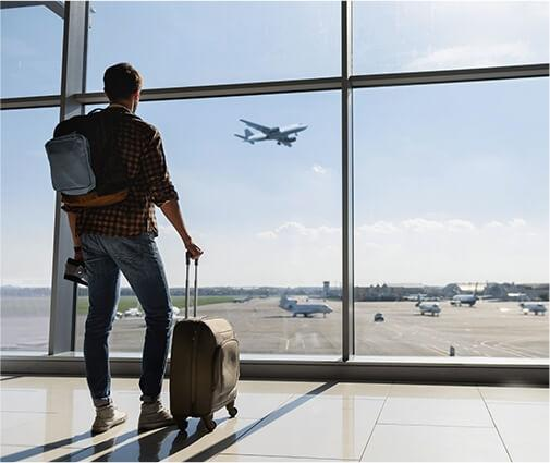 man in airport looking out window at plane taking off