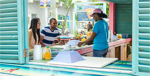 Bahamian Ambassador teaching a couple about local cusine.