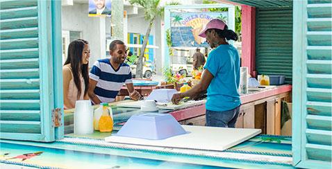 Bahamian Ambassador teaching a couple about local cusine.